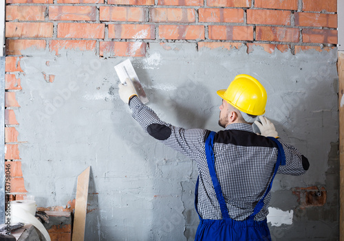 Craftsperson is plastering the wall © JackF