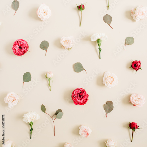 Flowers pattern texture made of beige and red roses, eucalyptus leaf on pale pastel beige background. Flat lay, top view. Floral texture background.
