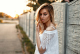 Pretty woman in a white lace T-shirt on the nature at sunset