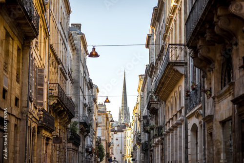 Fototapeta Beautiful morning street view with old buildings and tower of saint Michel cathedral in Bordeaux city, France