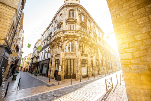Street view with beautiful buildings during the sunrise in Bordeaux city, France