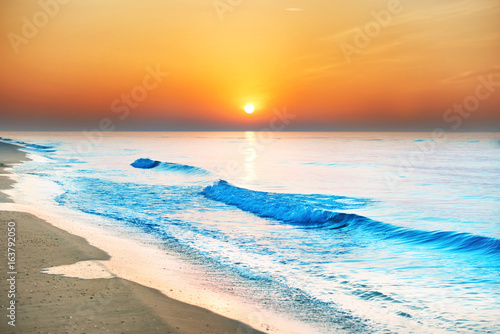 Sunset on the beach with long coastline