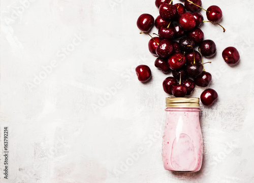 Foto op Aluminium Milkshake Sweet cherry yogurt in a glass bottle and fresg berries, top view