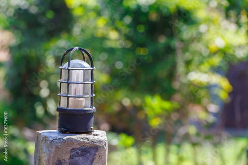 Poster Light bulb on concrete pole with green bokeh background.