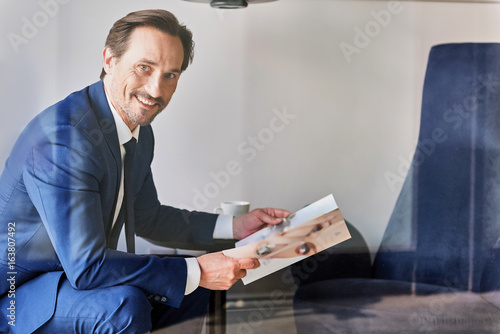 Confident businessman reading journal in restaurant Poster