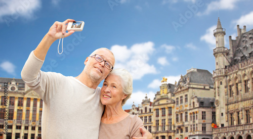 senior couple with camera traveling in brussels