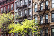 Sunlight shines on trees in front of historic old buildings on 3rd Avenue in the East Village of Manhattan, New York City