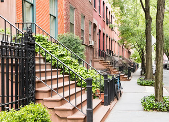 Scenic tree lined street of historic brownstone buildings in the West Village neighborhood of Manhattan in New York City, NYC USA