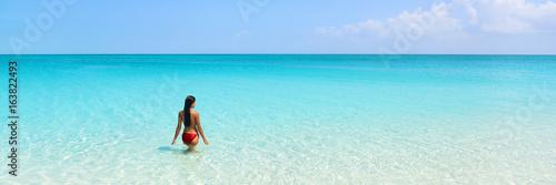 Beach luxury travel getaway resort vacation banner. Bikini woman relaxing enjoying tropical holidays swimming in turquoise ocean water in paradise destination.