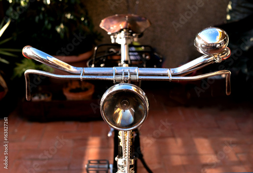 Vintage bike handlebar, with an antique light beacon, bell, brakes