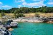 The rocky cliffs along the shoreline of Lake Travis make it a little
