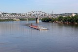 The barge headed up river on the boarders of Kentucky and Ohio. - 163838684