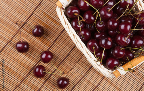 Ripe sweet cherry in the basket on a napkin