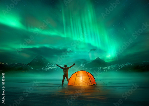 In de dag Noorderlicht A man camping in wild northern mountains with an illuminated tent viewing a spectacular green northern lights aurora display. Photo composition.
