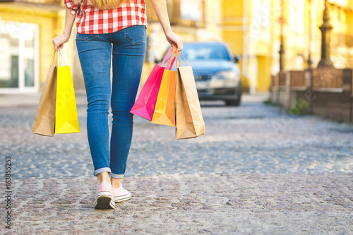 Portrait of young happy woman with shopping bags. Close-Up.