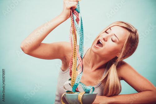Diet. Girl with colorful measuring tapes in bowl - 163870097