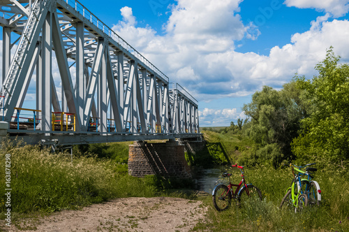 Bicycles stand on the ground near the water and near the railway bridge. Bicycle parts
