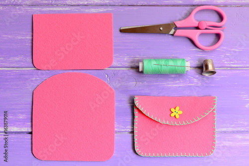 Children pink felt purse with yellow flower wooden button. Scissors, thread, needle, thimble on a wooden table. Easy homemade DIY made of felt. Top view