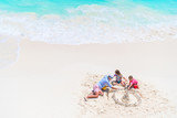 Fototapety Father and little daughters making sand castle at tropical beach