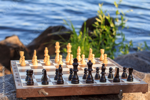 Poster Chess board with chess pieces on rock with river embankment background