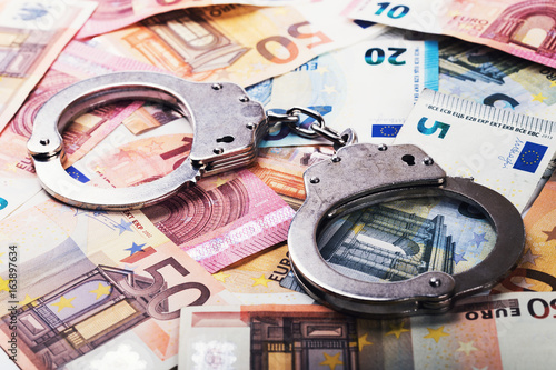 tax evasion, corruption concept - handcuffs on euro money bills