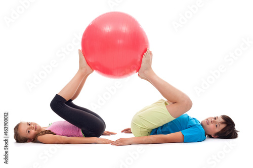 Young kids exercising with large rubber ball
