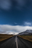 Starry night and empty driving road in Iceland with snowy mountains on the background