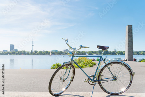 vintage blue bicycle parked at lakeshore of Alster Lake in Hamburg, Germany under beautiful clear blue summer sky with cityscape in blurred background