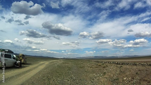 a Flying Bird in the Clouds Flies to the Cars and a Group of Men on Stony Dirt Roads in the Desert