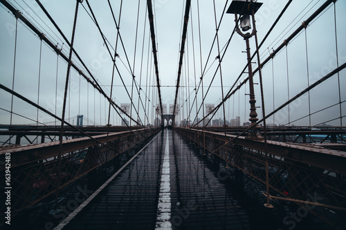 Brooklyn Bridge: Viewed down the center against NYC skyline on a rainy day