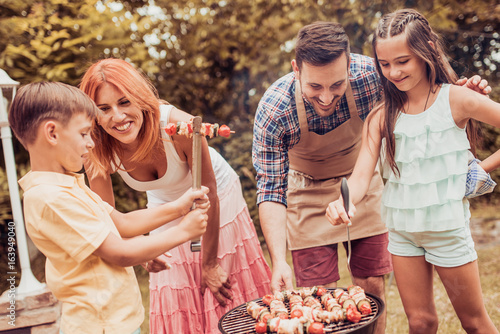 Happy family having a barbecue in their garden in summer