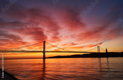 Poster clouds on fire on a sunrise in Lisbon, Portugal, with the April 25th Bridge