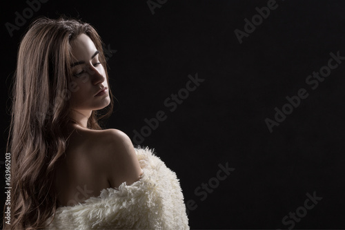 sad woman with bare shoulders in fur on black background