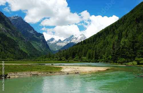 mountain valley and clear lake surface reflecting snow mountain and sky