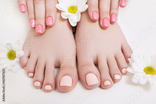 Tuinposter Pedicure Nude pedicure and manicure for spring. Woman hands and feet on white background closeup. Result of spa salon procedure