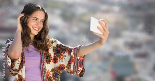 Millennial girl taking selfie against blurry city