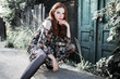 Stylish red-haired girl in a dress and pantyhose in a grid posing outside. Fashion Photo