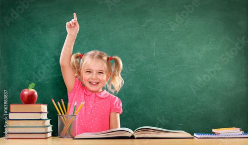 Fototapeta Happy Girl Raising Hand In The Classroom