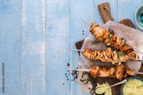 Chicken breast skewers with avocado sauce on blue wooden table - 164007604