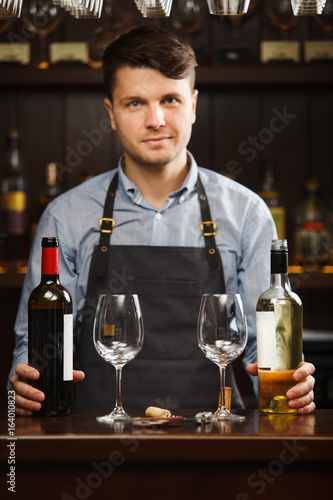 Sommelier with bottles of red and white wine and wineglasses © Ilshat