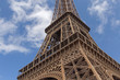 close up o Eiffel tower against blue sky with white clouds