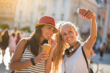 Two happy women are having nice time together in the city. They are taking selfie.