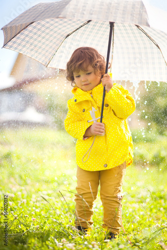 Leinwandbild Motiv Adorable little girl eith umbrella. Rainy autumn day