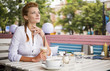 Young dreamy beautiful red hair woman sits in summer cafe, looks out on the street and drinks hot coffee latte from cup.