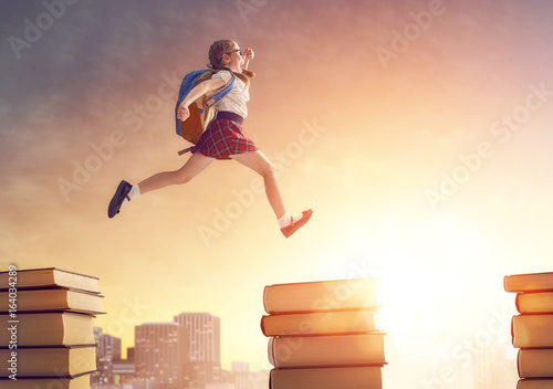 child running and jumping on books