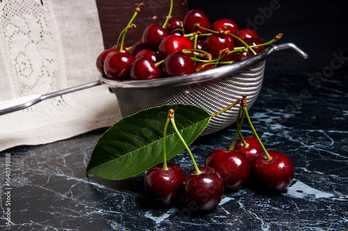 Several red sweet cherries and big green leaf on the table. Fresh organic cherry in colander on dark marble background..