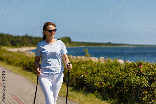 Nordic walking - middle-aged woman working out  - 164045061