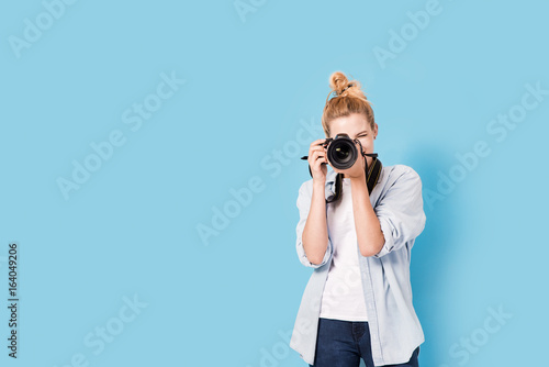 Fototapeta Young blonde photographer is taking a photo. Model isolated on a blue background with copy space
