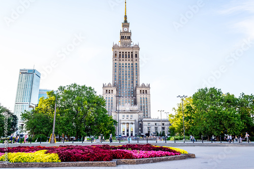 Palace of culture and science in Warsaw on sunny day with blue sky and green trees.  - 164060206