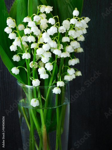 Bouquet of lilies of the valley in a glass vessel on a dark background